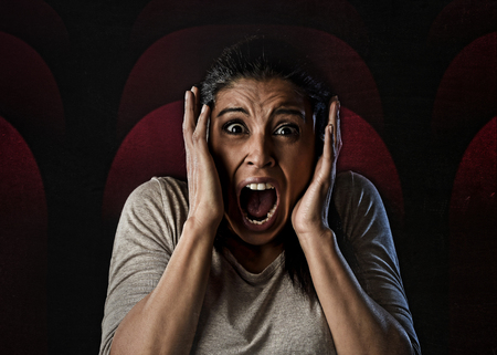 primal: portrait young attractive Latin woman desperate and scared terrorized at cinema hall watching horror movie looking horrified in panic  screaming in primal fear emotion face expression Stock Photo
