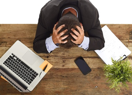 devastated: desperate stressed businessman sitting at office laptop computer desk with hands on his head crying devastated and frustrated in overwork and business crisis concept