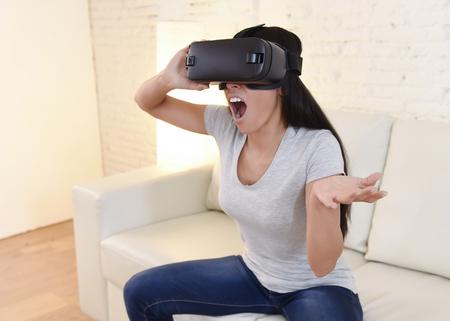 joven y atractiva mujer feliz en el hogar sofá de la sala de estar sofá emocionado con gafas 3D viendo 360 visión de realidad virtual disfrutando de la diversión experiencia cibernética en el concepto de realidad simulación vr