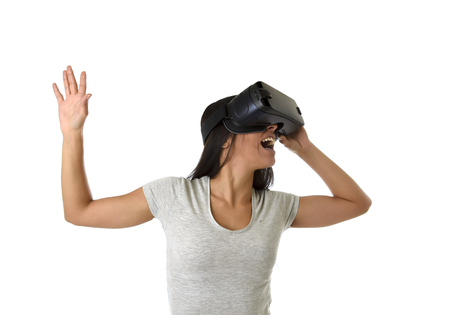 young attractive happy woman excited using 3d goggles watching 360 virtual reality vision enjoying cyber fun experience in vr simulation reality and new gaming technology isolated white background Stock Photo