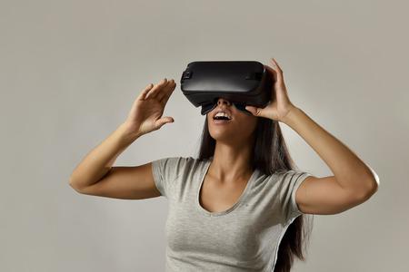 Joven atractiva feliz mujer emocionada utilizando 3d gafas de observación 360 visión de la realidad virtual disfrutar de la experiencia divertida cib en vr simulación de la realidad y la tecnología de los juegos nuevos aislados fondo gris