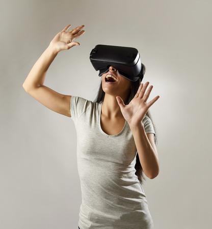 jeune femme heureuse attrayante excitée utilisant des lunettes 3D à regarder 360 vision de la réalité virtuelle en appréciant expérience amusante cyber dans la réalité de simulation vr et nouvelle technologie de jeu isolé sur fond gris