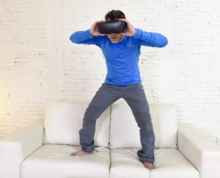 joven moderno en casa de pie en el sofá de la sala de estar sofá emocionado usando gafas 3d viendo la realidad virtual 360 visión disfrutando de la diversión experiencia cibernética en el concepto de realidad simulación vr