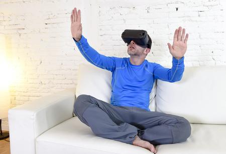 el hombre moderno joven en el hogar salón sofá cama excitado usando gafas 3D que mira 360 visión de realidad virtual disfrutando de la experiencia cibernética de diversión en realidad vr concepto de simulación