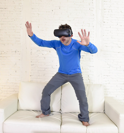 young modern man at home standing on living room sofa couch excited using 3d goggles watching 360 virtual reality vision enjoying the fun cyber experience in vr simulation reality concept Foto de archivo