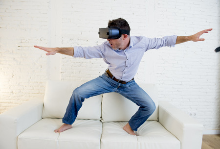 young modern man at home standing on living room sofa couch excited using 3d goggles watching 360 virtual reality vision enjoying the fun cyber experience in sea surfing vr simulation reality