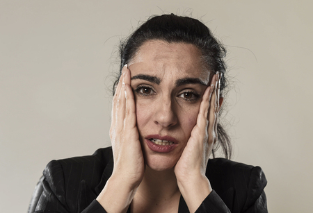 close up face of young business woman in office suit suffering migraine pain and strong headache with fingers on her tempo in business stress and work problem isolated on even background Stock Photo