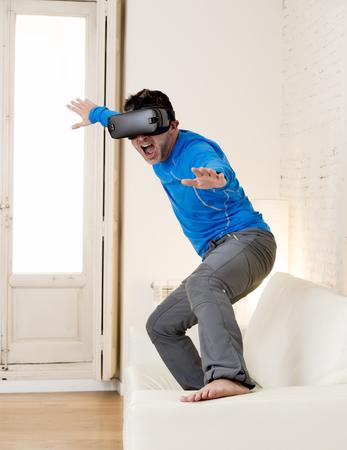joven hombre moderno en el hogar de pie en la sala de estar Sofá sofá excitado con gafas 3D observando la visión de realidad virtual 360 disfrutar de la experiencia cibernética diversión en el mar de surf vr simulación de realidad