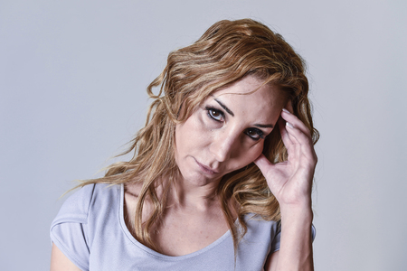 blond attractive woman on her thirties sad and depressed looking at the camera in sorrow and grief facial expression in female depression emotion concept isolated on grey background