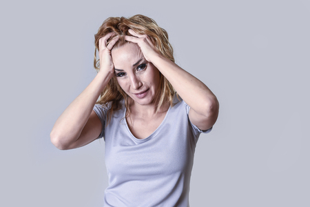 blond attractive woman on her thirties sad and depressed looking desperate in sorrow and grief facial expression in female depression emotion concept isolated on grey background Stock Photo