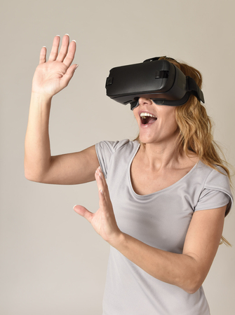 young attractive blond woman wearing headset VR virtual reality vision goggles watching video happy amazed and shocked in new advanced technology experience in gaming concept