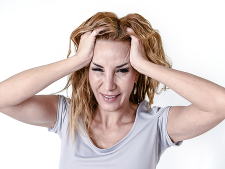 blond attractive woman on her thirties sad and depressed looking desperate in pain face expression suffering migraine and headache in depression and emotional crisis concept isolated on white Stock Photo