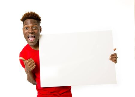 young attractive and happy afro american black man holding and showing blank panel billboard with copy space for adding advertising message text isolated background Stock Photo
