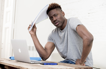 maybe: young attractive african american man sitting at home living room working with laptop computer and paperwork looking stressed and desperate maybe studying for exam in education concept