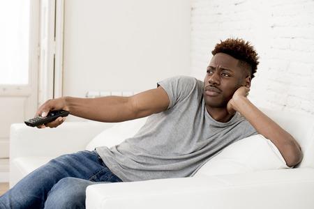 805334656  73903068 - Joven apuesto y atractivo hombre afroamericano negro sentado en  casa sofá sofá viendo la televisión usando tv control remoto cambiar  canales ...