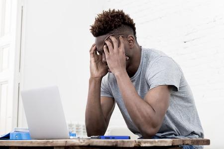 junge attraktive African American Mann zu Hause sitzen Wohnzimmer mit Laptop-Computer und Papierkram suchen gestresst und verzweifelt möglicherweise für die Prüfung im Bildungskonzept studieren