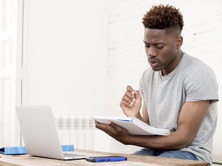 maybe: young attractive african american man sitting at home living room working with laptop computer and paperwork looking concentrated maybe studying for exam in education concept