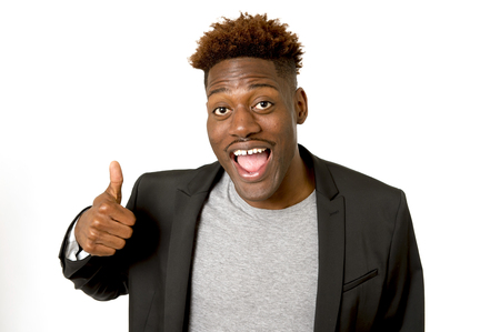 young friendly and happy afro american man smiling excited and posing cool and cheerful wearing suit jacket isolated on white background looking positive in intense happiness facial expression