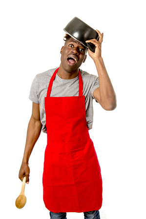young desperate and confused black afro american man in chef apron holding cooking pot in his head and spoon looking lost and overworked in male home cook concept isolated on white background