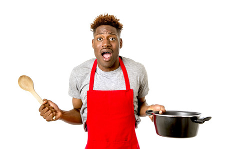 young desperate and confused black afro american man in chef apron holding cooking pot and spoon in his hands looking lost and overworked in male home cook concept isolated on white background Stock Photo