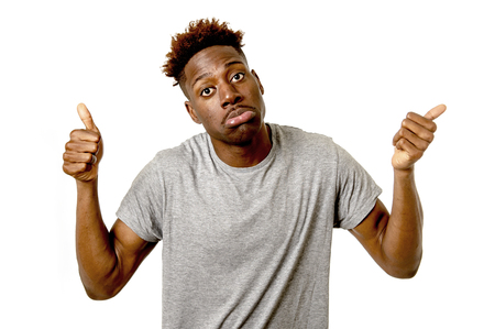 young funny black afro american man looking sad but gesturing happy giving thumb up in contradiction with his sadness face expression looking isolated on white background