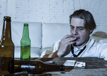 beer and necktie: wasted alcoholic and drug addict man with loose tie snorting cocaine and drinking beer bottles at home living room couch in toxic substance addiction and abuse concept