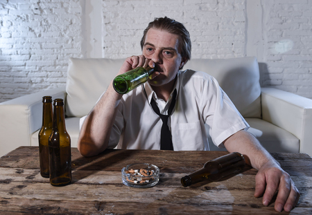 beer necktie: wasted dirty and messy alcoholic man on loose necktie at home living room couch drinking beer bottle getting drunk and intoxicated in alcohol abuse and addiction and alcoholism problem