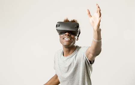 young happy and excited afro american man wearing virtual reality vr 360 vision goggles enjoying video game isolated on clear background in innovation and gaming technology concept