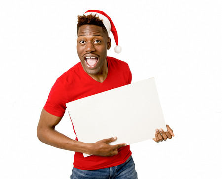young attractive black afro american man in Christmas Santa hat smiling happy and showing blank billboard with copy space for adding xmas advertising text isolated on white in sales and offer concept Stock Photo