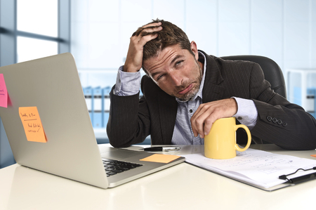 tired businessman: tired and frustrated businessman desperate face suffering stress and headache at computer desk busy with paperwork overwhelmed and stressed  at modern office business financial district Stock Photo