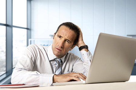 tired businessman: desperate senior businessman in crisis working on computer laptop at office desk in stress under pressure facing work problems at modern office in business district