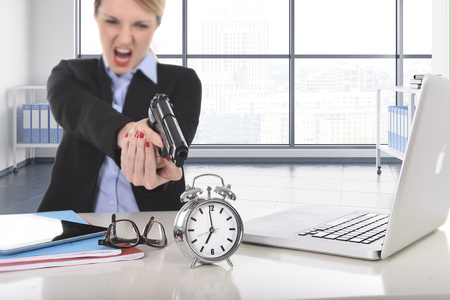 career timing: young attractive businesswoman furious and angry working with computer laptop pointing gun to alarm clock in out of time, long hours of work and project deadline stress Stock Photo