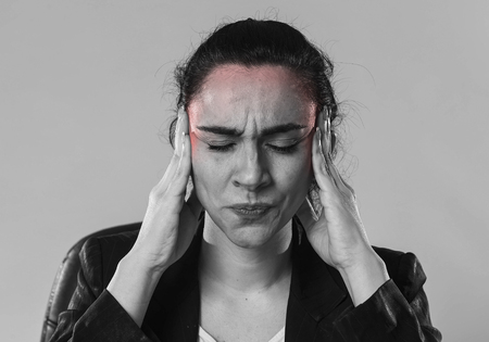 black and white close up face of young business woman in office suit suffering migraine pain and strong headache with fingers on her tempo in business stress and work problem isolated background Stock Photo