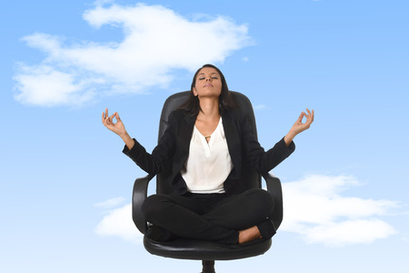young beautiful latin american business woman sitting at office chair in lotus posture practicing yoga and meditation isolated as if floating or flying on blue sky background Stock Photo - 81148474