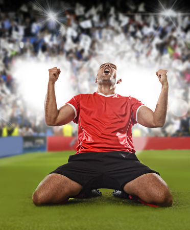 young happy and excited football player in red jersey celebrating scoring goal kneeling on grass pitch doing victory sign with fists isolated on soccer pitch stadium composite background