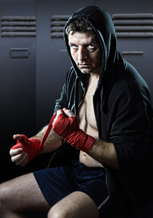 young man in boxing hoodie jumper with hood on head sitting wrapping hands and wrists getting ready for fighting posing concentrated isolated on dark gym locker room background