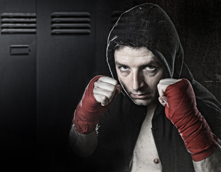 young man in boxing hoodie jumper with hood on head wearing hand and wrist wrapped ready for fighting posing isolated on gym locker room grunge dirty background with angry face expression