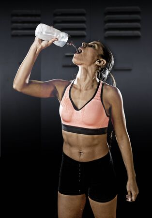 young beautiful and fit latin sport woman in fitness clothes drinking water tired during training workout in healthy lifestyle concept isolated on gym locker room dark background