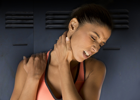 young attractive hispanic fitness woman touching and grabbing her neck and upper back suffering cervical pain isolated on gym locker room background in sport injury and body health care concept