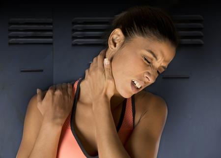 Jonge aantrekkelijke spaanse fitness vrouw aanraken en grijpende haar nek en bovenste rug lijden cervicale pijn geïsoleerd op sportschool kleedkamer achtergrond in sport letsel en lichaam gezondheidszorg concept