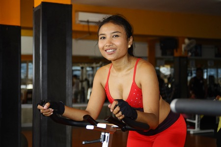 young beautiful sweaty Asian happy  woman training smiling hard cycling and riding on static bike workout at gym in sport fitness body care and healthy lifestyle concept and bicycle fitness gear