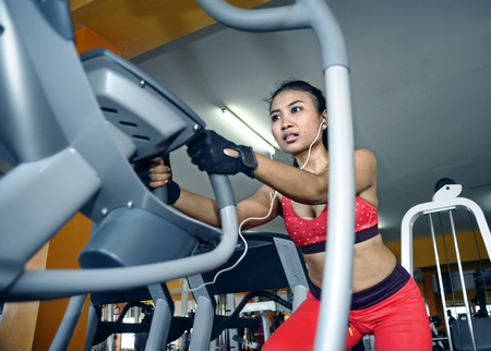 young sexy and sweaty Asian woman training hard at gym using elliptical pedaling machine gear in intense workout exercise wearing sport top and gloves in fitness and healthy lifestyle concept Stock Photo