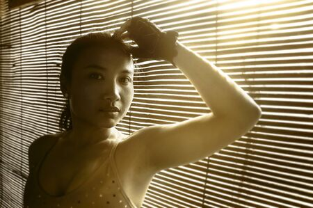 sexy asian woman: shady portrait of young beautiful Asian woman in gym sport cloths posing in Venetian blinds background in shadow sun dramatic light posing thoughtful and pensive in artistic beauty concept Stock Photo