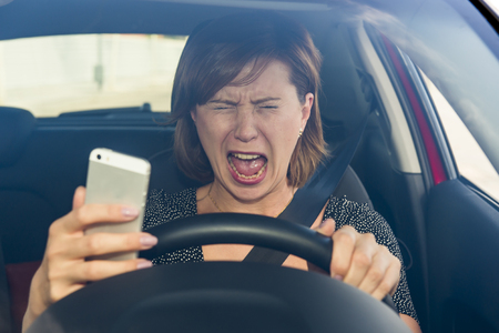 young beautiful woman  driving car while texting and using mobile phone distracted in risk and danger of accident crashing by distraction and not paying attention to traffic