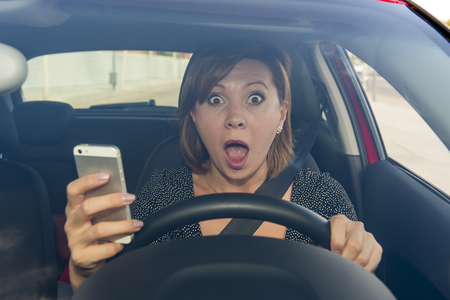 young beautiful woman  driving car while texting and using mobile phone distracted in risk and danger of accident crash by distraction and not paying attention to traffic
