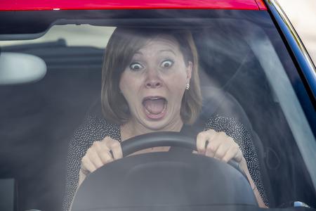 debiutantka nowy kierowca młoda piękna kobieta przestraszona i zestresowana podczas jazdy samochodem w strachu i szoku mimika krzycząca w panice