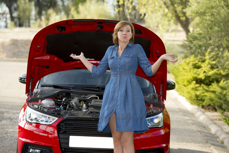 young attractive desperate and confused woman stranded on roadside looking worried to broken car engine failure or crash accident in automobile road assistance and insurance concept Stock Photo