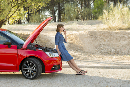 waiting phone call: young attractive desperate and confused woman stranded on roadside with broken car engine failure crash accident calling on mobile phone for mechanic assistance in insurance company concept