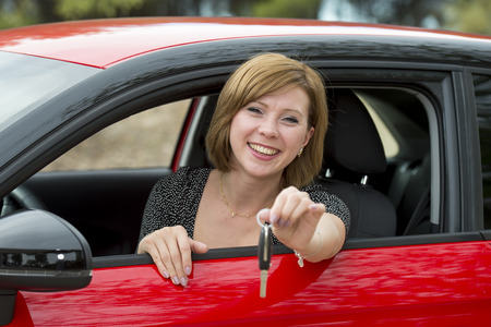 windows: young happy attractive woman smiling proud sitting at driver seat holding and showing car key in new automobile buying and renting concept and insurance and rental advertising