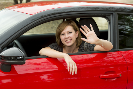 windows: young happy attractive woman sitting at driver seat smiling cheerful and proud waving hello from new automobile in buying and renting concept and insurance or rental advertising